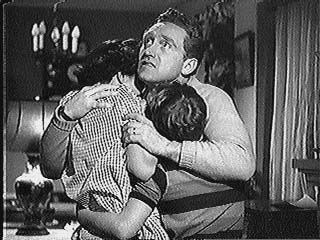 Joe Smith holds his family during a rain storm